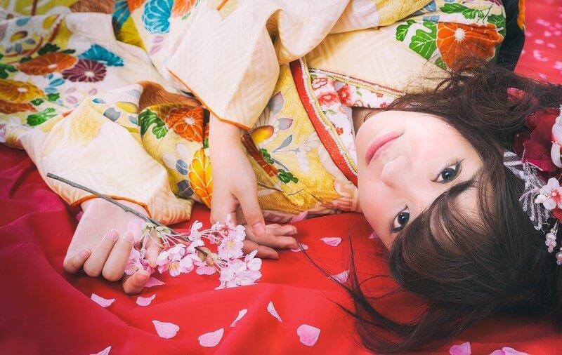 桜散る毛氈に寝転がる振袖美女